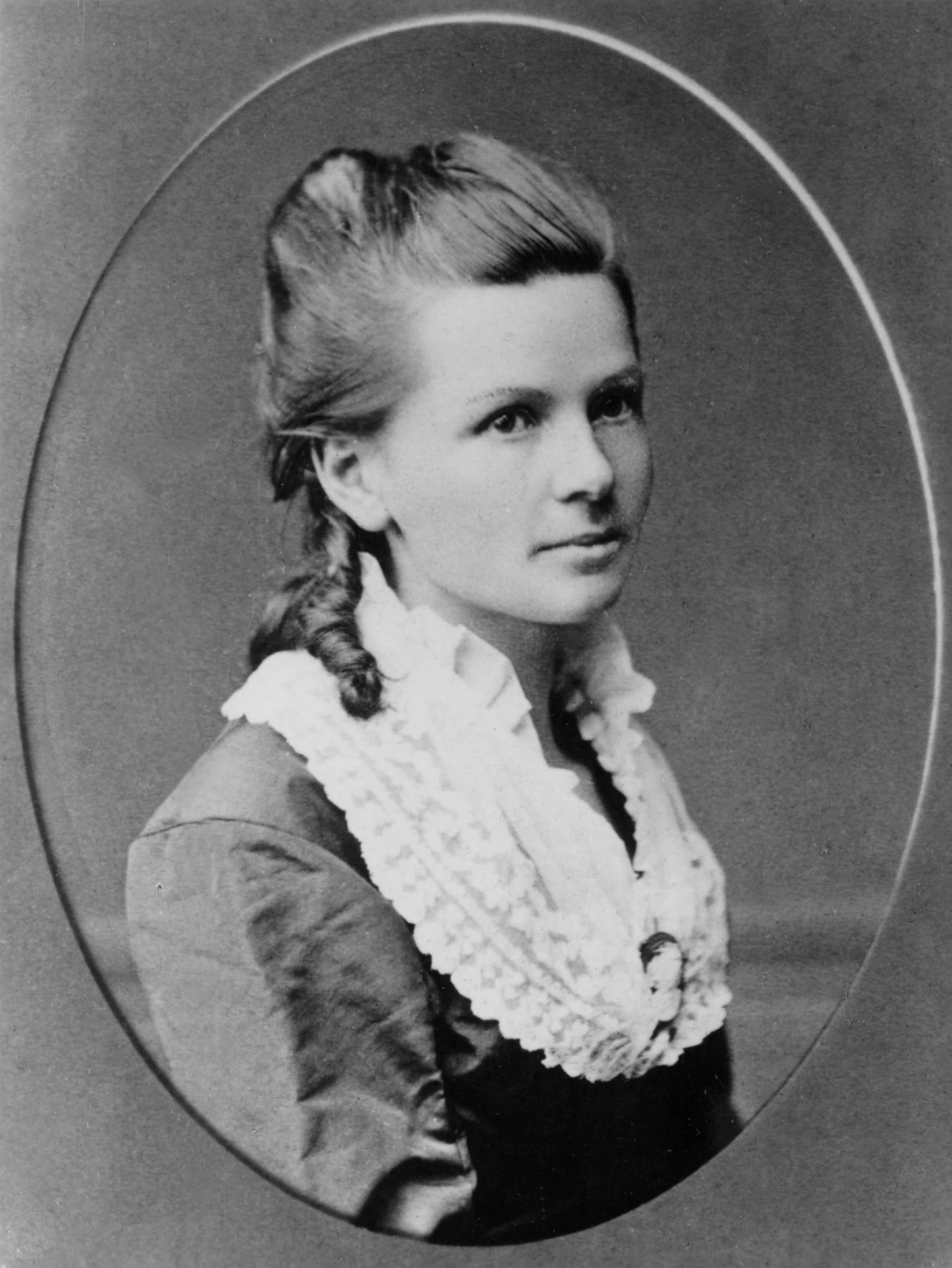 Cette photographie en noir et blanc est  un portrait de Bertha Benz dans un cadre ovale. La jeune fille porte une veste sombre avec un large col blanc de dentelle ; ses cheveux sont coiffés en mèches anglaises.