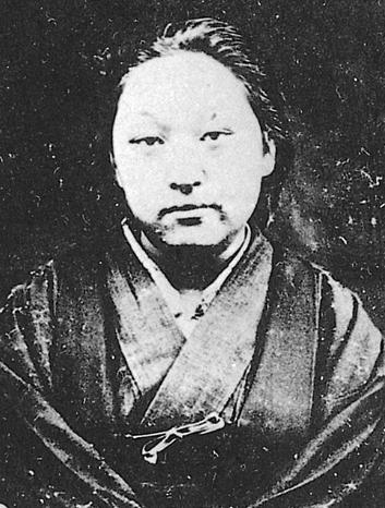 Cette photographie en noir et blanc montre Fukuda Hideko. Elle porte des vêtements traditionnels japonais et ses cheveux sont retenus en arrière.