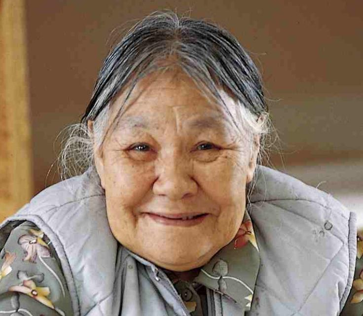 Ce photographie montre l'artiste Kenojuak Ashevak à l'âge de 70 ans. Ses cheveux grisonnants sont tirés en arrière. Elle regarde directement la caméra et sourit.