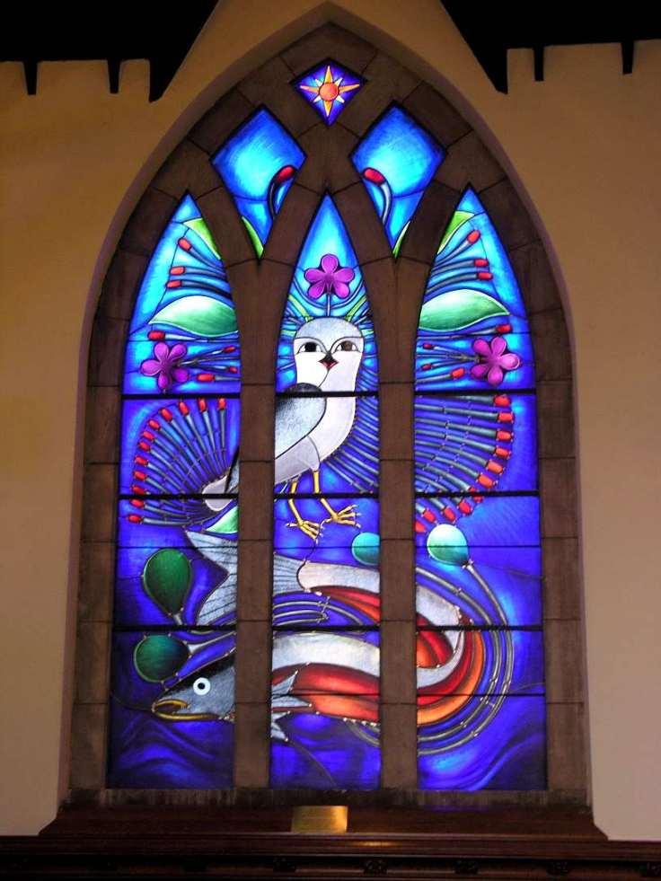 Cette photographie montre un vitrail designé par Kenojuak Ashevak. Sur fond bleu, le vitrail représente un oiseau stylisé aux longues plumes surplombant un poisson nageant dans l'eau.