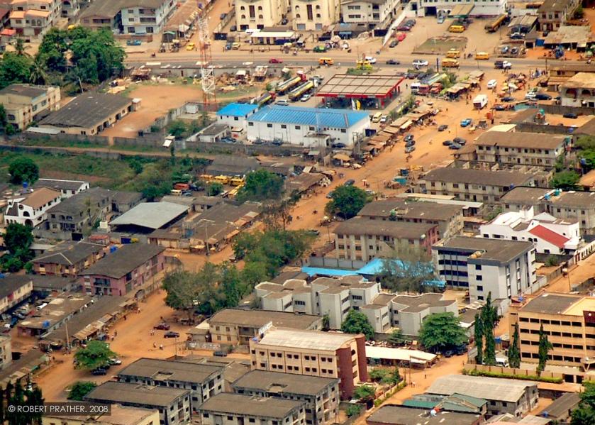 Cette photographie est une vue aérienne de la ville de Lagos au Nigeria ; on voit les toits des bâtiments et des rues de terre rouge.