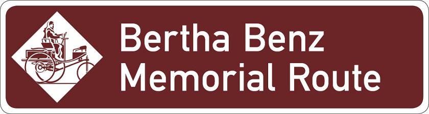 Cette image montre le panneau de signalisation de la Bertha Benz Memorial Route ; y figurent le nom de la route et, à gauche, un dessin stylisé représentant Bertha Benz sur le tricycle Benz 3.