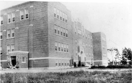 Cette photographie en noir et blanc montre le pensionnat autochtone de Shubenacadie. C'est un grand bâtiment rectangulaire de briques, avec des rangées de fenêtres rectangulaires et un jardin devant.
