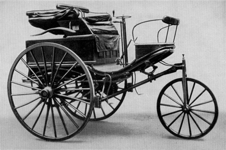 Cette photographie en noir montre le tricycle Benz 3, modèle utilisé par Bertha Benz lors de son voyage. Le véhicule possède une roue directrice à l'avant et  deux plus grandes roues à l'arrière, surmontées par le siège du conducteur.