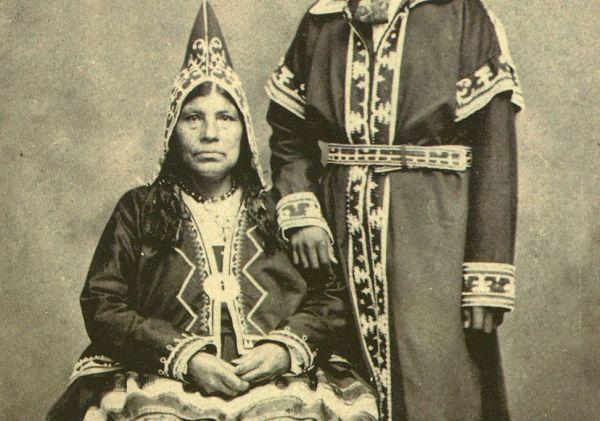 Cette photographie en noir et blanc montre un couple de Mi'kmaqs, une femme assise et un homme debout, la main sur son épaule. Ils sont tous les deux habillés de vêtements traditionnels, avec des robes et tuniques longues. La femme porte un bonnet triangulaire décoré.