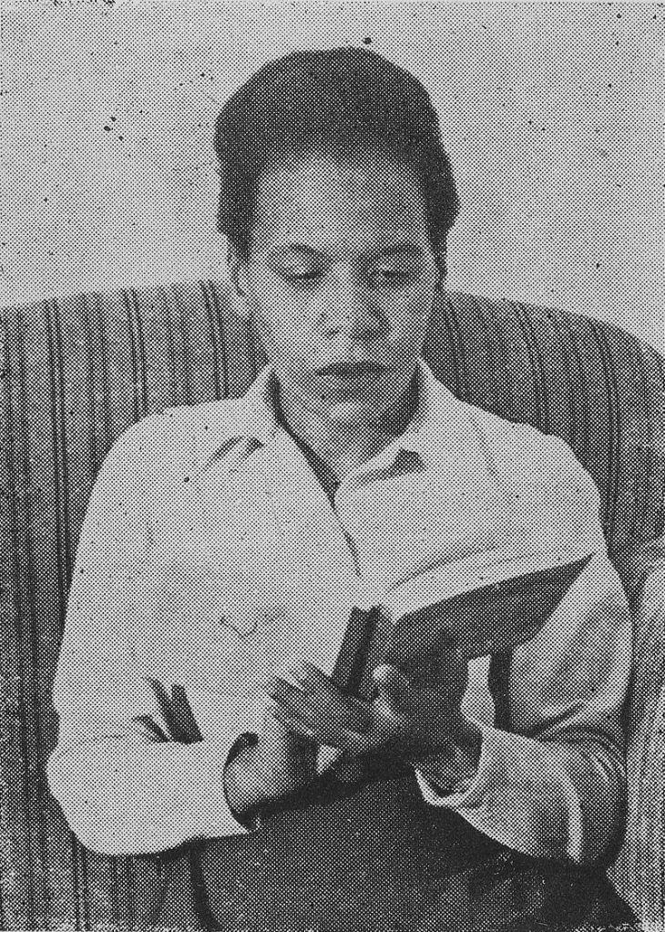 Cette photographie en noir et blanc montre Virginia Brindis de Salas, assise sur un canapé, absorbée dans la lecture d'un livre ouvert entre ses mains. Elle porte une chemise claire.