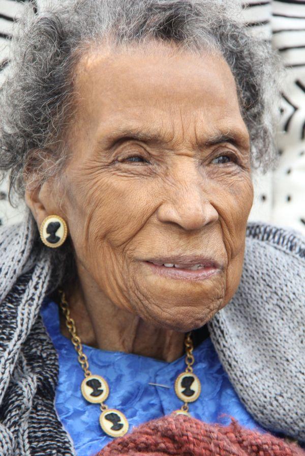 Cette image est un portrait d'Amelia Boyton Robinson, en 2015, à l'âge de 103 ans. Elle a les cheveux gris et un visage souriant. Elle porte une chemise bleue sous un vêtement épais de laine. Elle porte des camées représentant un profil de femme noire en collier et en boucle d'oreille.