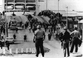 Cette photographie en noir montre plusieurs policiers en uniforme, avec casques et armes, attendant face à un pont. En face, des manifestants de la première marche de Selma arrivent.