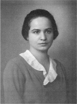 Photographie en noir et blanc de Marietta Blau. Elle porte ses cheveux sombres tirés en arrière. Elle porte un vêtement à col blanc.