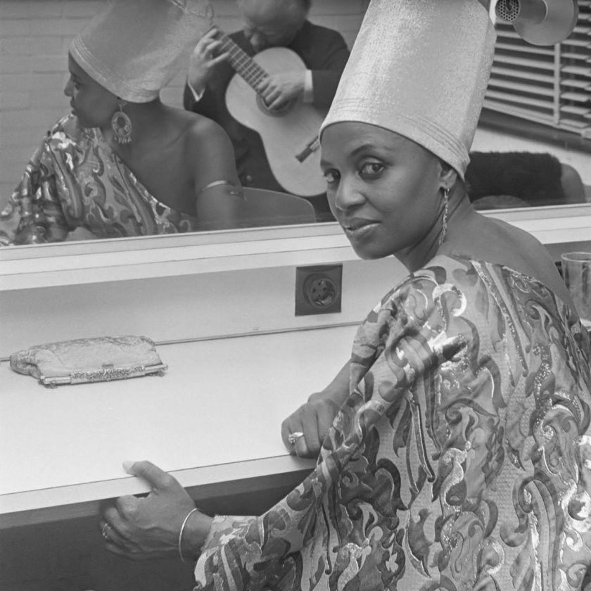 Cette photo en noir montre Miriam Makeva assise devant un miroir, à moitié tournée vers la caméra. Elle porte un tissu et une coiffe africains, un bracelet, des bagues et des boucles d'oreille. Dans le miroir, à côté du reflet de Miriam Makeba, on discerne le reflet d'un musicien en train de jouer de la guitare.