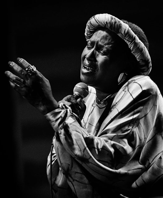 Cette photo en noir et blanc montre Miriam Makeba en train de chanter, micro à la main. Absorbée par sa prestation, elle a les yeux fermés, les lèvres ouvertes et la main gauche levée, tandis que l'autre tient le micro.