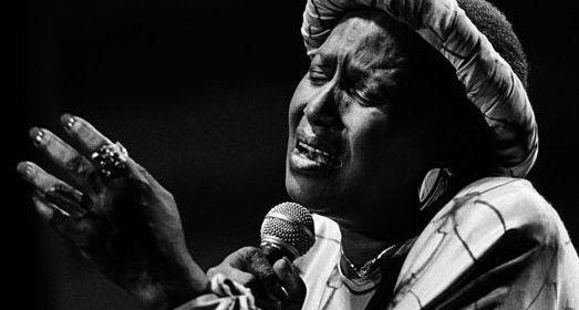 Cette photo en noir et blanc montre Miriam Makeba en train de chanter, micro à la main. Absorbée par sa prestation, elle a les yeux fermés, les lèvres ouvertes et la main gauche levée, tandis que l'autre tient le micro.