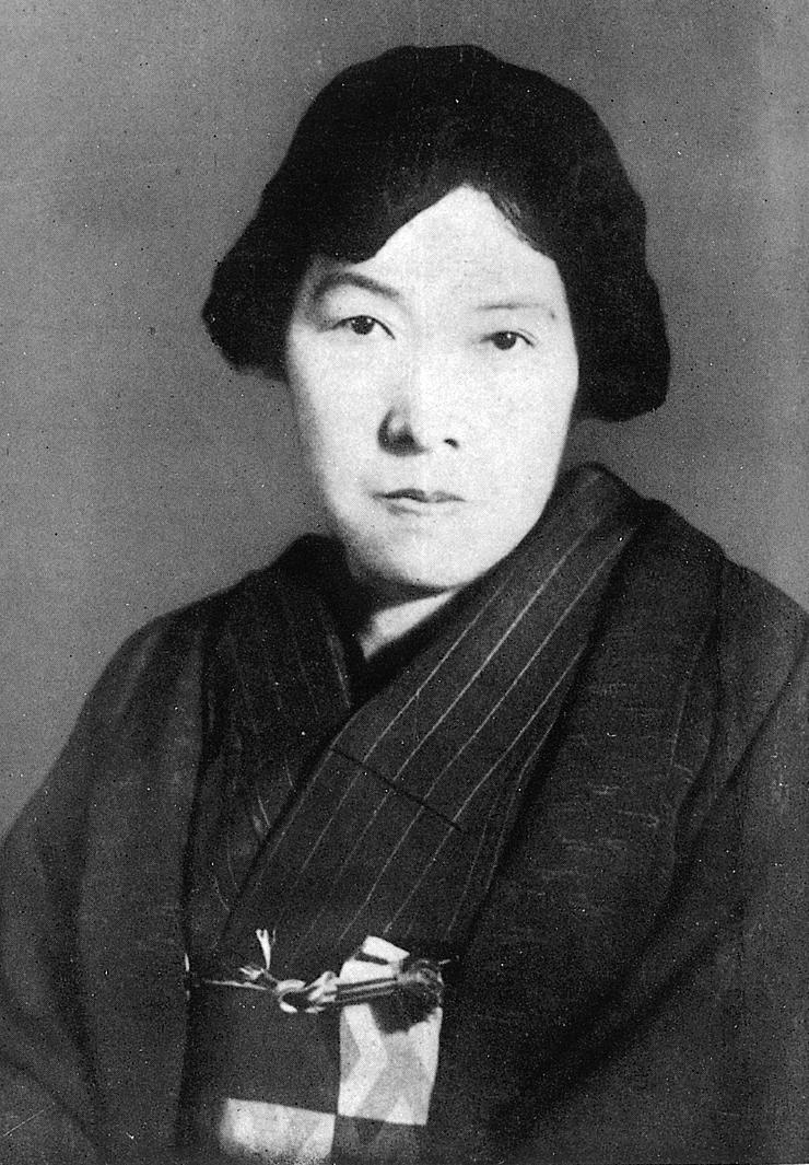 Cette image en noir et blanc est une photographie de Yosano Akiko. Vêtue d'un kimono, elle porte ses cheveux noirs retenus en arrière. Regardant l'objectif, elle affiche un air sérieux.