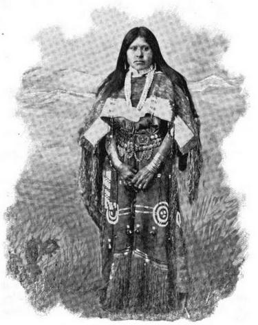 Cette image en noir et blanc montre Chipeta en pied. Elle est vêtue de vêtements traditionnels Utes, avec une jupe à frange et une veste aux manches amples. Elle porte ses longs cheveux lisses libres, jusqu'aux épaules.