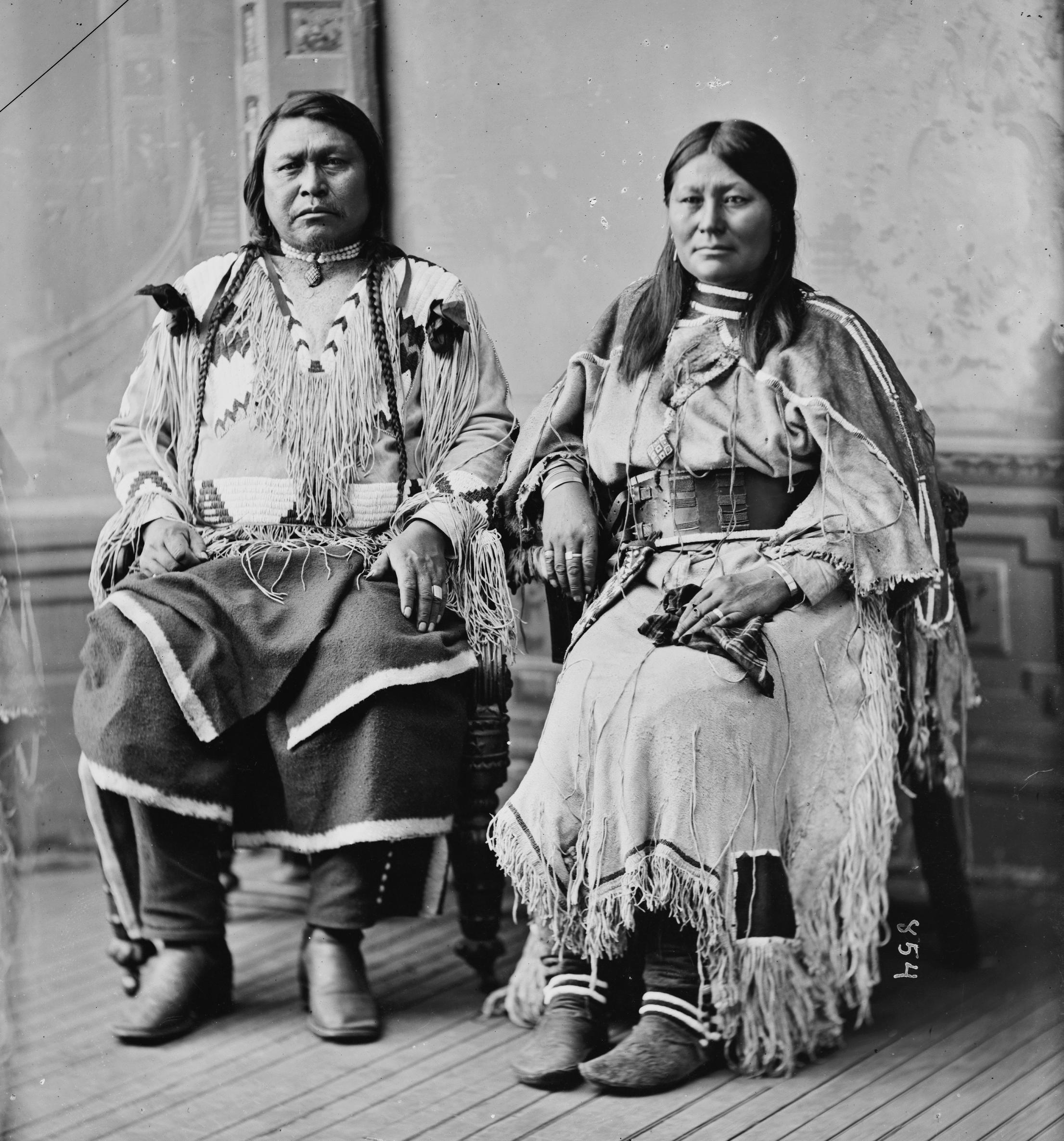 Cette photographie en noir et blanc montre Ouray et Chipeta assis côte à côte, Ouray à gauche et Chipeta à droite. Ils sont tous deux habillés en vêtements traditionnels utes. Chipeta porte une jupe à perles qu'elle a réalisée elle-même.