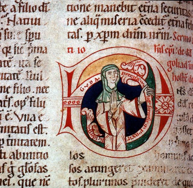 Cette image est extraite de l'homiliaire de Saint Barthélémy, copié et enluminé par Guda. On y voit le texte en latin, écrit en noir et rouge. Au centre, Guda s'est dessinée dans un D en lettrine, en habit de religieuse.