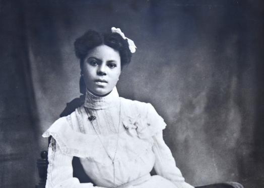 Cette photographie en noir et blanc montre Lucile Buchanan, assise sur une chaise en bois et vêtue d'une robe blanche sophistiquée avec des manches longues. Le bras droit appuyé sur un accoudoir de la chaise, elle regarde directement la caméra.