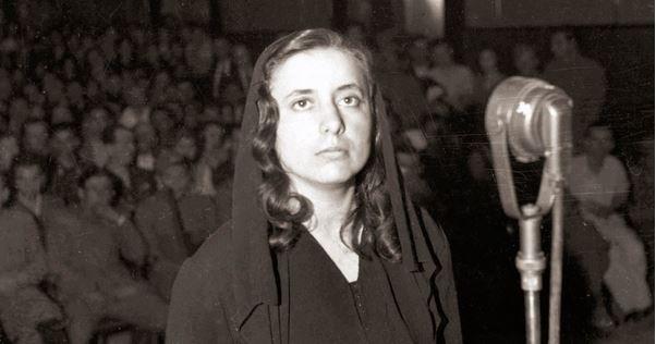Cette photographie en noir montre Musine Kokalari lors de son procès en 1946. Au premier plan, elle se tient debout devant un micro, vêtue d'habits sombres et un voile couvrant ses cheveux. Elle a l'air grave. Derrière elle, à l'arrière plan, des rangs de spectateurs assis et debout assistent au procès.