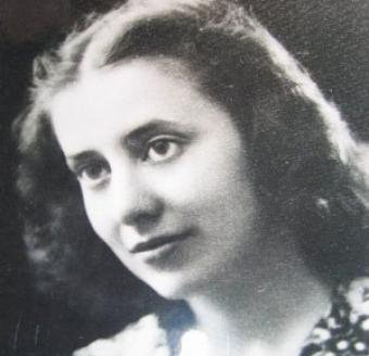 Cette photographie en noir et blanc montre le visage de Musine Kokalari. Elle porte ses cheveux sombres lâchés, aux épaules. Tournée vers la gauche, elle a de grands yeux et un très léger sourire.