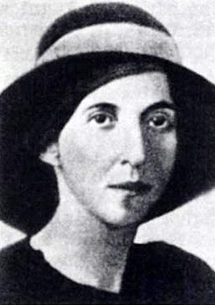 Cette photographie en noir et blanc montre Urani Rumbo. Elle est cadrée aux épaules et porte un haut noir ainsi qu'avec un chapeau entouré d'un ruban clair.