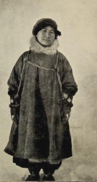 Cette photographie en noir et blanc montre Ada Blackjack en pied. Elle porte un manteau épais, de la fourrure autour du cou et un manteau.