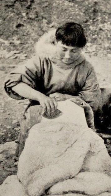Cette photographie en noir et blanc montre Ada Blackjack assise ; elle est occupée à enlever la graisse d'une peau de phoque.