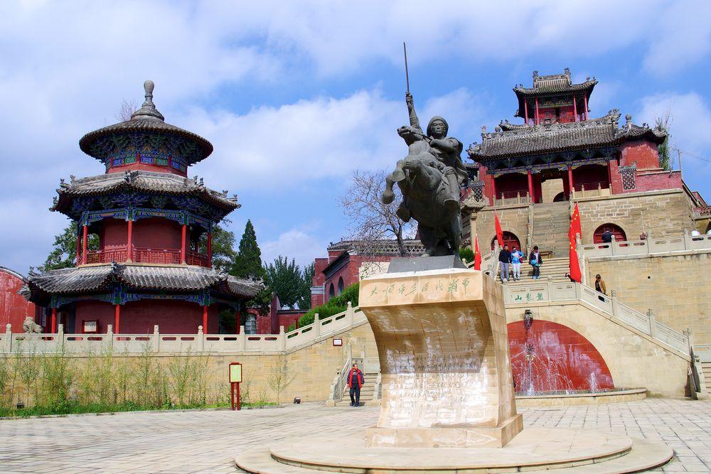Cette photographie montre le Palais temporaire de Li Zicheng dans le Shaanxi. Au premier plan, une statue d'un combattant à cheval. Derrière, des escaliers montent vers deux bâtiments rouges aux toits sombres.