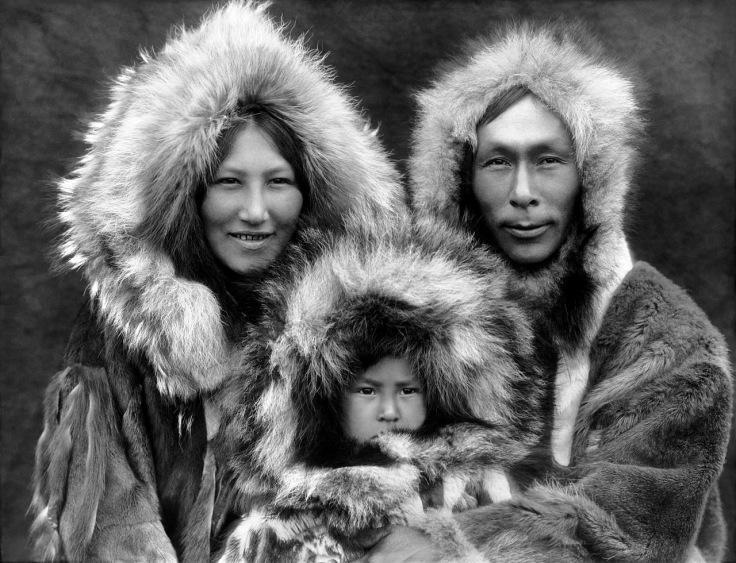 Cette photographie en noir et blanc montre une famille inupiat, en Alaska (en 1929). On y voit une femme à gauche, un homme à droite et un jeune enfant entre les deux. Tous les trois portent des capuches de fourrure et des vêtements chauds.