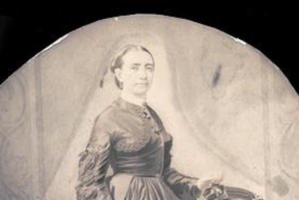 Cette image est une aquarelle en noir et blanc représentant Kate Warne debout devant un fauteuil, vêtue d'une robe sombre et longue à la jupe large, la main gauche posée sur le fauteuil. Elle a les cheveux tirés en arrière.