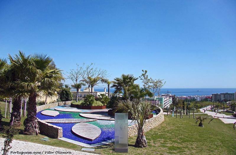 Cette photographie montre un monument à Alda do Espirito Santo dans un parc au Portugal. Au premier plan, le monument avec des bassins et des palmiers, à l'arrière-plan la mer.