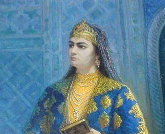 Cette illustration montre Nadira, vêtue d'une robe bleue et jaune. Elle porte une couronne, un collier avec de nombreux rangs de perles, des bracelets et des bagues. Un voile recouvre ses cheveux. Elle tient un livre entre ses deux mains.