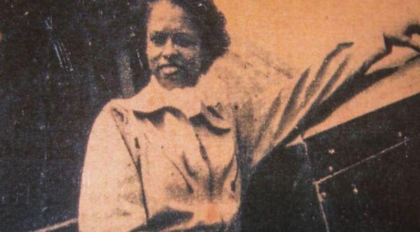 Cette image est une vieille photographie montrant Azellia White devant une avion, la main gauche posée sur l'avion. Elle sourit.