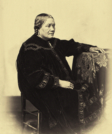 Cette image est une photographie en noir et blanc de la reine Pomare IV. Elle est assise sur une chaise, la main gauche posée sur une table. Elle est vêtue d'un long vêtement sombre.