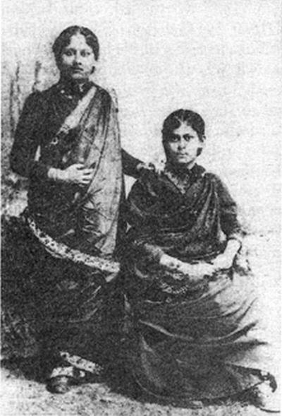 Cette image montre Sarala Devi Chaudhurani et sa sœur Hironmoyee. Habillée de robes traditionnelles indiennes, elles sont côte à côte, l'une est assise et l'autre debout.