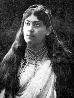 Cette image en noir et blanc est un portrait de Sarala Devi Chaudhurani. Elle porte ses longs cheveux noirs lâchés, recouvrant ses épaules. Elle a des bijoux autour du cou et dans sa chevelure.