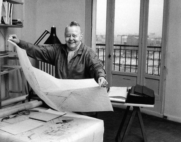Cette photo en noir et blanc de Robert Doisneau montre Charlotte Perriand dans son atelier (à l'age de 78 ans). Installée derrière un bureau couvert de papiers et de crayons, elle tient un grand schéma des deux mains. Elle est vêtue d'une chemise, prote ses cheveux en chignon et affiche un large sourire. Derrière elle, une fenêtre permet de voir un environnement urbain.