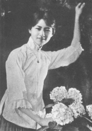Cette photographie en noir et blanc montre Lin Huiyin vêtue d'une jupe plissée et d'une chemise claire. Ses cheveux sont retenus en chignon. Son bras gauche est levé, son bras droit tient un bouquet de fleurs.