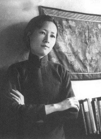 Cette image en noir et blanc montre Lin Huiyin vêtue d'une chemise sombre, bras croisés. Cheveux retenus en chignon, elle se tient devant un mur  sur lequel est accrochée une tapisserie. A côté d'elle, une étagère de livres.