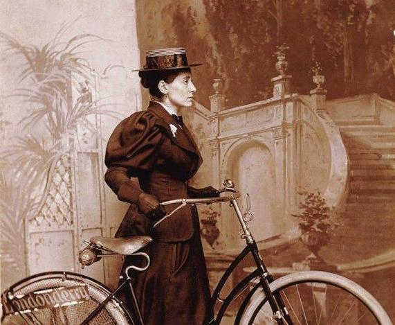 Cette photographie montre Annie Londonderry debout, vêtue d'une longue robe sombre et d'un chapeau à ruban, tenant par le guidon un vélo. Elle est devant un arrière-plan montrant un escalier monumental et des arbres.