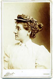 Cette image est une photographie en buste d'Annie Londonderry - Annie Cohen Kopchovsky. Vêtue d'une chemise blanche, elle porte un chignon élaboré et un chapeau et regarde vers la gauchhe.