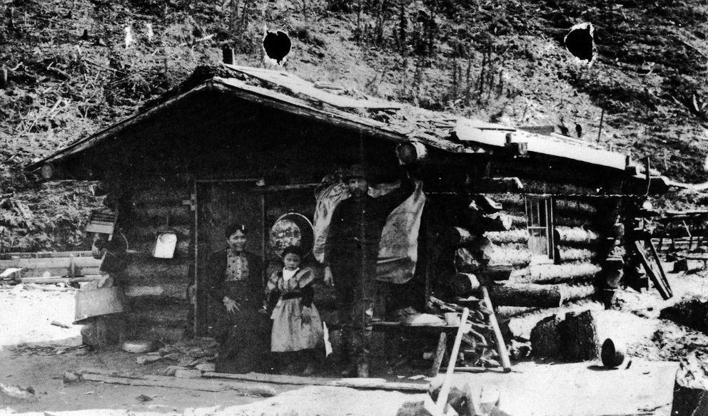 Cette photographie en noir et blanc montre Kate Carmack, Graphie Carmack et George Karmak devant leur cabane de bois. Kate est assise devant la porte tandis que sa fille et son mari se tiennent debout.