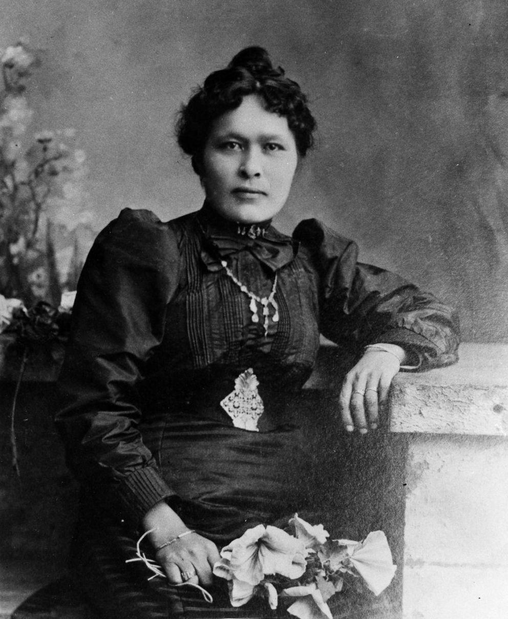 Cette photographie en noir et blanc  montre  Shaaw Tláa - Kate Carmack en riches vêtements occidentaux. Elle porte une longue robe sombre, une ceinture et un collier ouvragés et tient un bouquet de fleurs à la main.