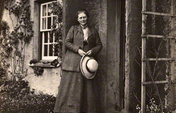 Cette image en noir en blanc montre Beatrix Potter devant sa maison. Vêtue d'une longue jupe sombre et d'une veste assortie, elle tient un chapeau de paille entre ses mains.