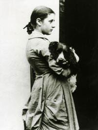 Cette photographie en noir et blanc montre Beatrix Potter à l'âge de 15 ans. De profil, vêtue d'un long manteau, les cheveux retenus en chignon, elle tient un chien dans ses bras.