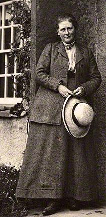 Cette photographie en noir et blanc montre Beatrix Potter, debout devant sa maison. Elle est vêtue d'une jupe longue et d'une veste et tient un chapeau entre ses mains.