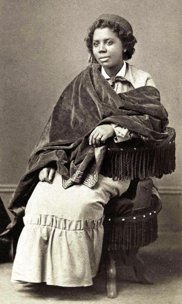 Cette image est une photographie en noir et blanc d'Edmonia Lewis. Elle est assise sur un fauteuil et porte une longue robe. Son buste est couvert d'un grand châle sombre.