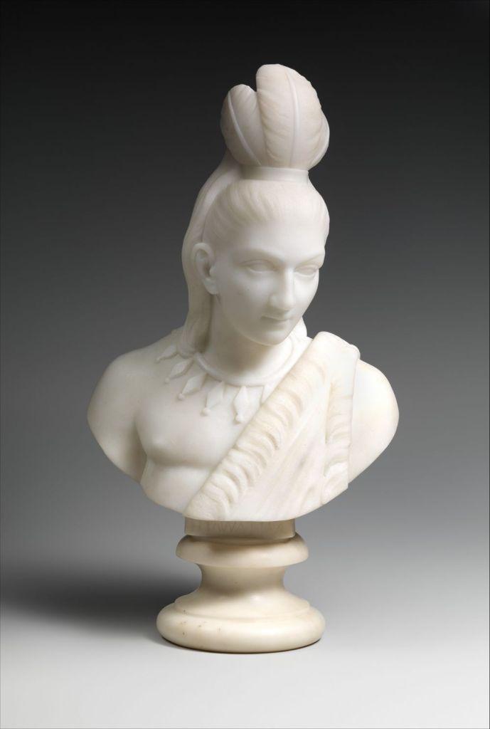 Cette image montre l'oeuvre Hiawatha d'Edmonia Lewis ; il s'agit d'un portrait en buste de marbre d'une personne amérindienne portant une coiffe, un collier et un vêtement traditionnels.