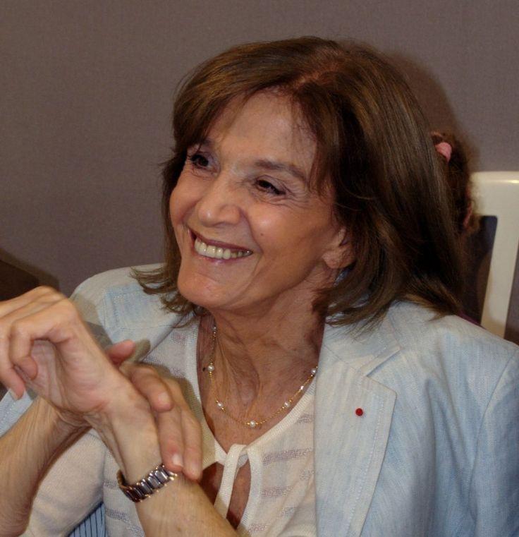 Cette photographie est un portrait de Gisèle Halimi en 2008.  Elle est assise, porte un haut blanc et une veste bleue sur les épaules. Ses coudes sont posés sur une table devant elle. Elle sourit.