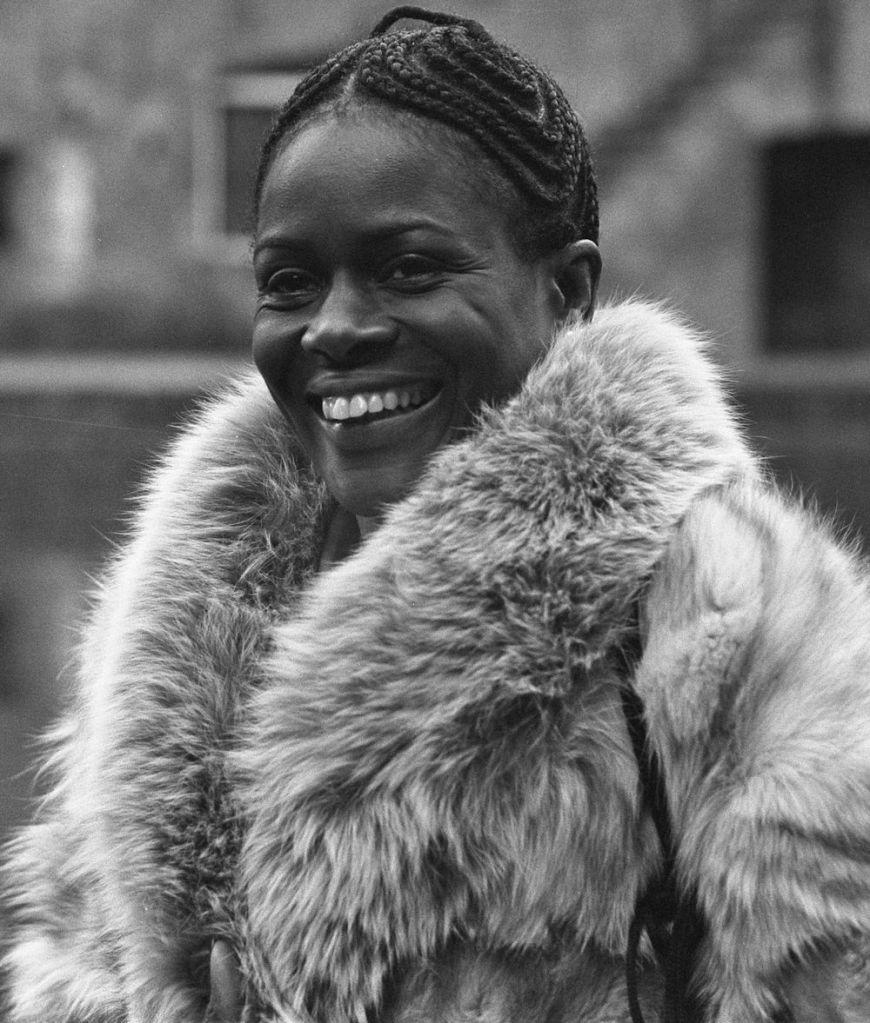 Cette image est un portrait en noir et blanc de Cicely Tyson en 1973. Elle porte un manteau. Ses cheveux sont noués en tresses près du crâne. Elle a un large sourire.
