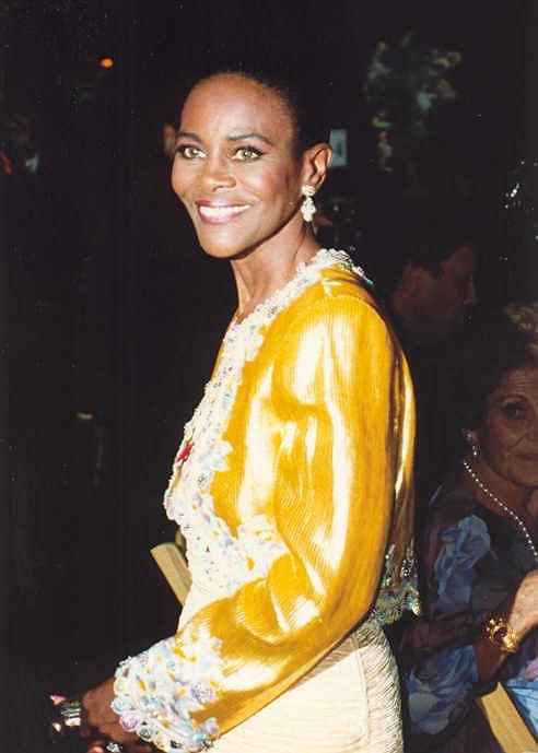 Cette photo est un portrait de Cicely Tyson en 1992. Elle porte une veste jaune brodée aux manches et aux contours, et des boucles d'oreille. Elle a un grand sourire.